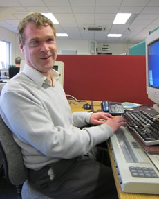 Photo of James Bowden at his desk in the Dolphin Development office, complete with Braille display!