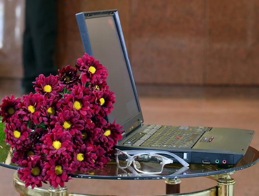 Laptop on table with bunch of flowers and pair of glasses