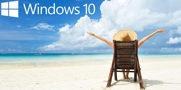 Windows 10 logo in the blue sky.  Lady sat on a deckchair on the beach, arms overhead.