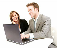 Photo of a man working on a laptop sat with a lady smiling.