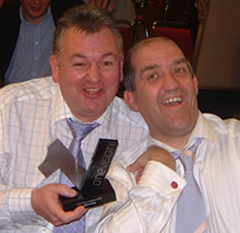 Photo of Noel Duffy and Dave Salisbury of Dolphin celebrating with the One Vision award in their hands.