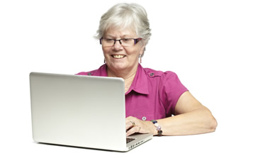 Photo of a lady smiling while using a laptop computer