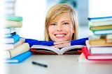 Photo of a female student looking between two piles of text books with her chin on the desk